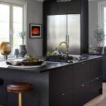 Kaunis musta keittiö, jossa teräksen värinen jääkaappipakastin