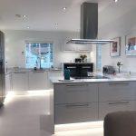 Iso valkoinen keittiö ja teräksen väriset kodinkoneet
